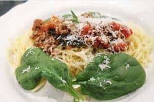homemade beef mince sauce on spaghetti with fresh spinach leaves