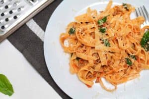 Tagliatelle with minced beef and tomato sauce on a white dinner plate with fresh herbs