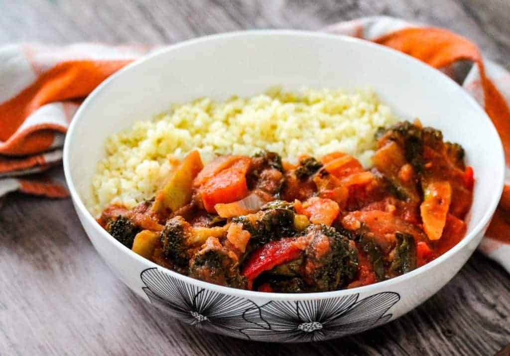 One of the best vegetarian recipes for spicy veggie stew with couscous in a white bowl on a wooden table.