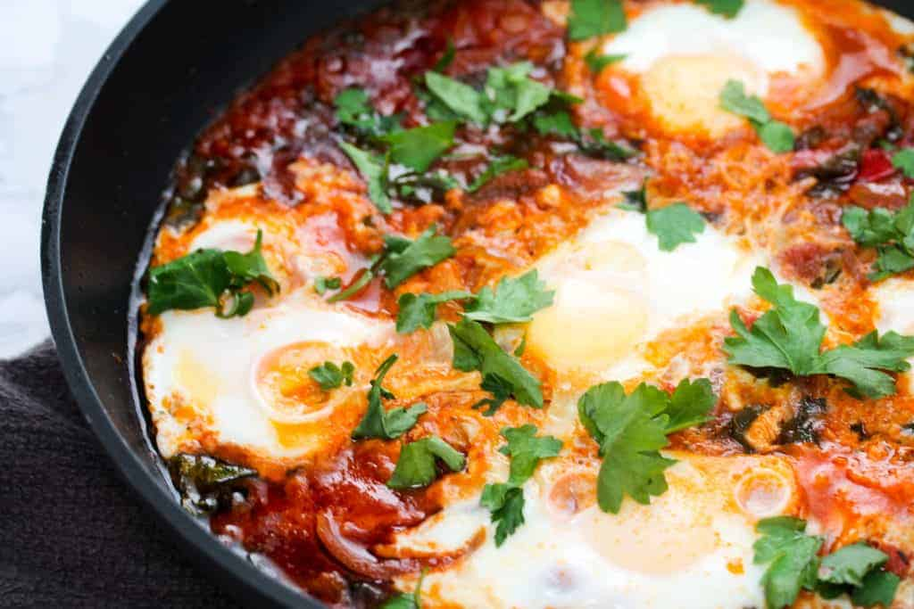 close up on shakshuka in a cast iron skillet with poached eggs and toomato sauce