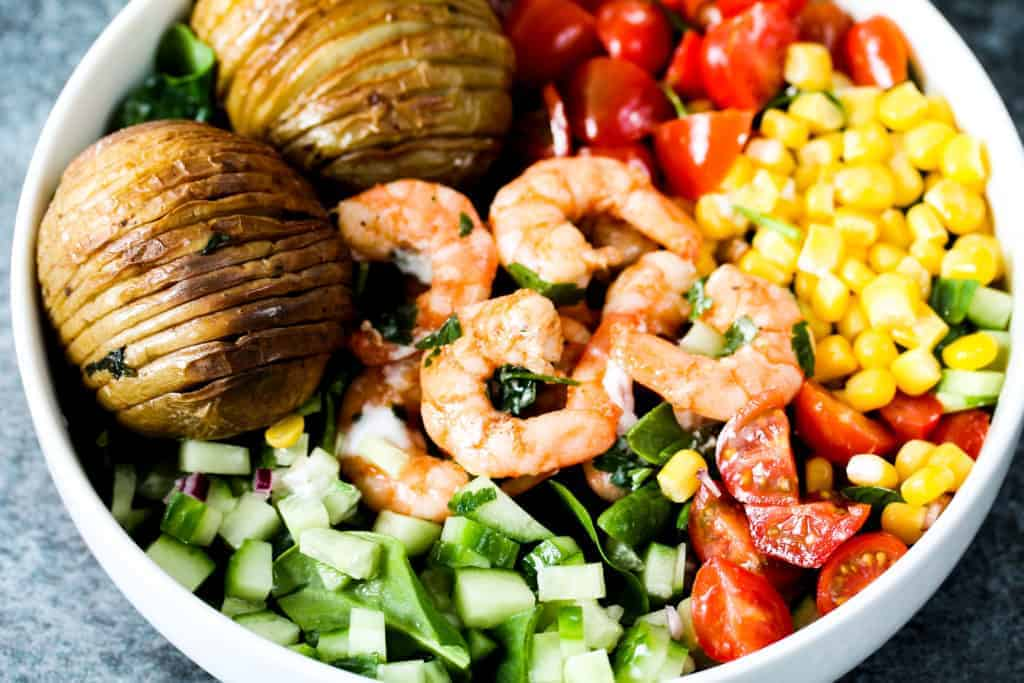 hasselback-potatoes-served-with-prawns-and-veggies