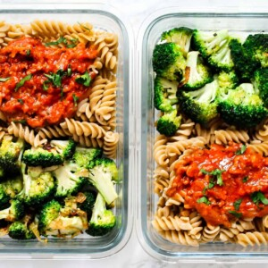 Minced-beef-sauce-and-pasta in two glass meal prep containers with steamed broccoli florets