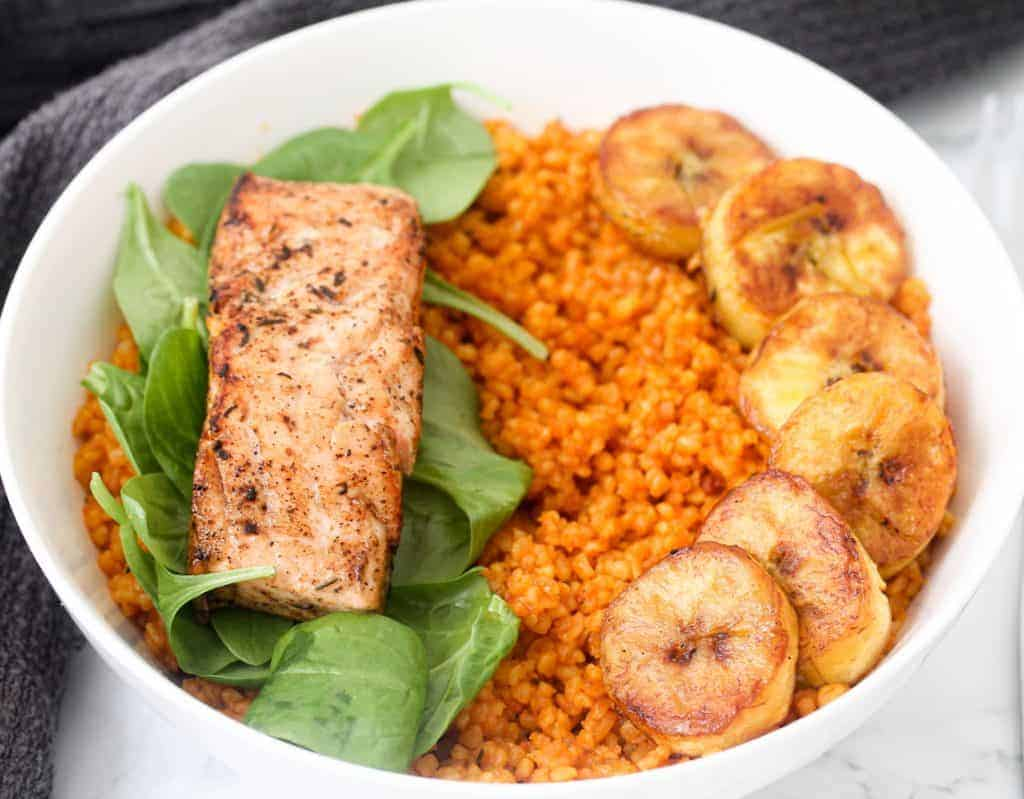 Jollof bulgur wheat served with spinach, plantain and salmon birds eye view