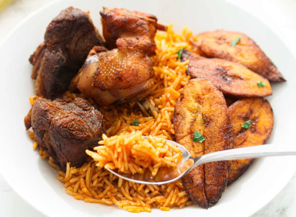 A spoon of jollof rice from a plate