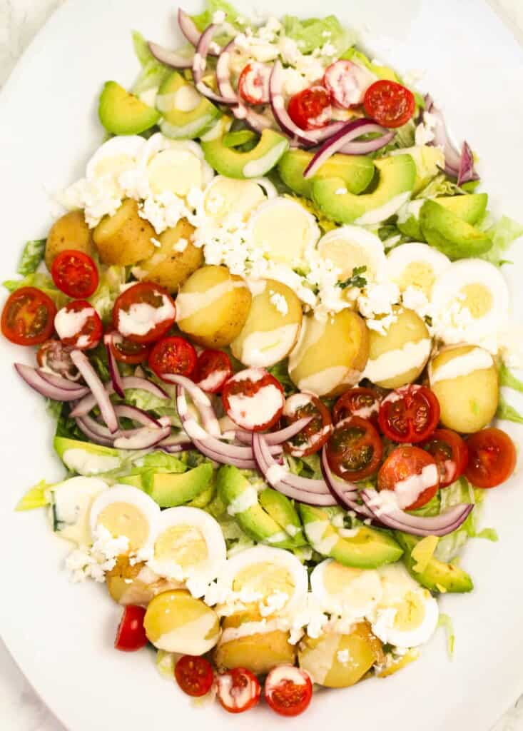 baby potato cobb salad in a white plate
