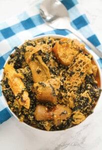 efo elegusi in a white bowl with a blue cloth