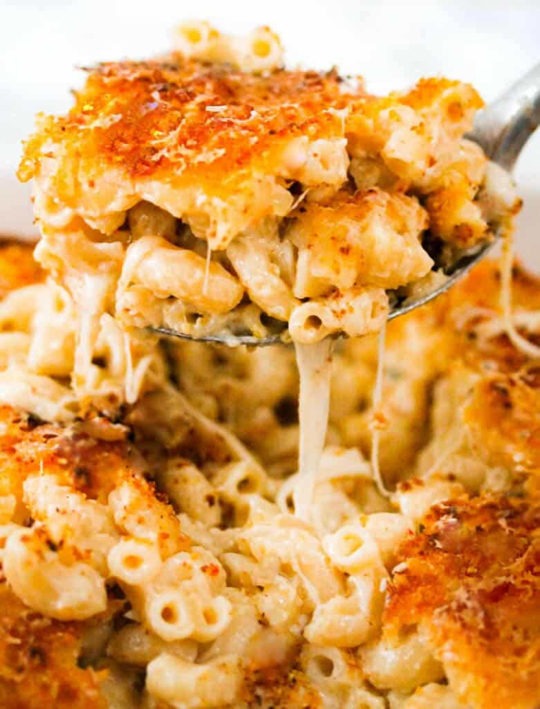 5-cheese macaroni in a silver spoon with cheese hanging down