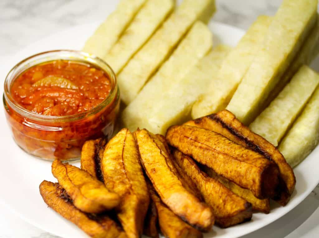 dun dun served with pepper sauce, and plantain in a white plate