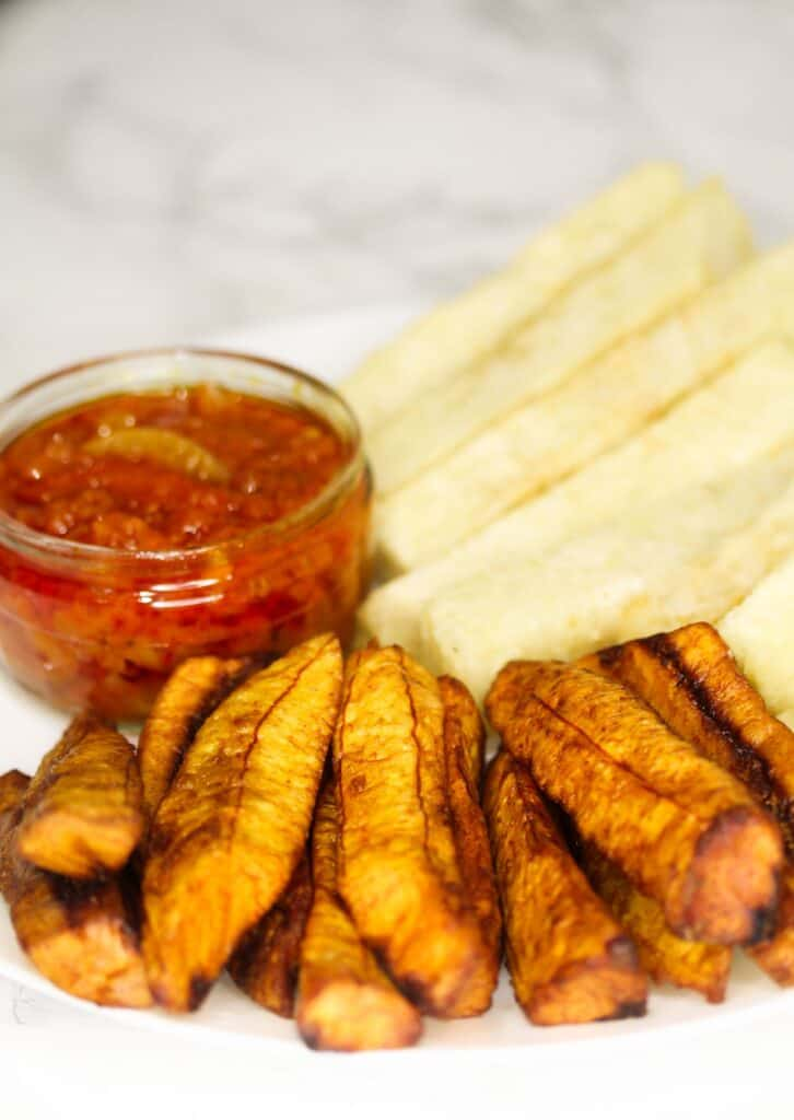 fried yam served with plantain, and pepper sauce in a plate