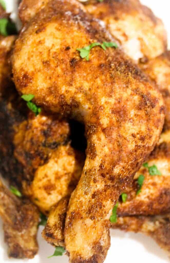 Spicy grilled suya chicken leg with fresh herbs
