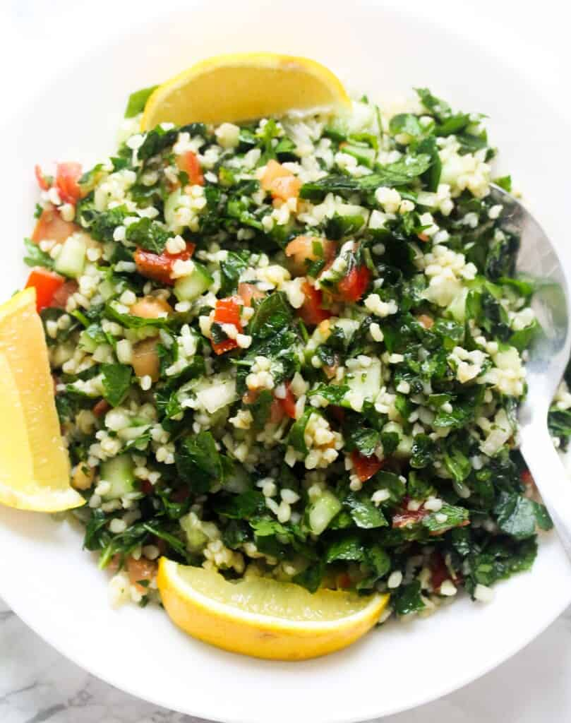 tabbouleh salad with lemon wedges on a white plate with a serving spoon
