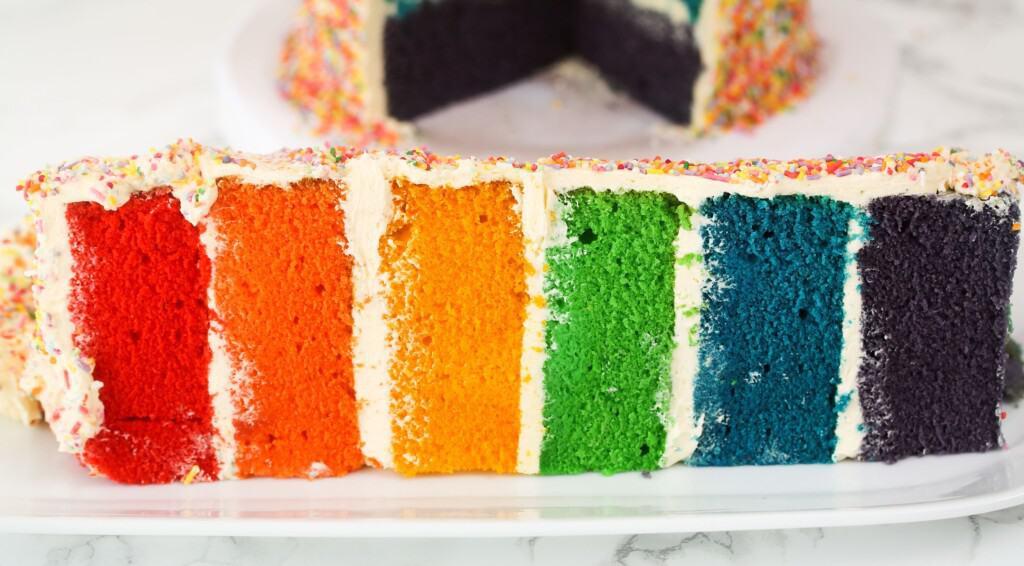 slice of layered rainbow cake with sprinkles