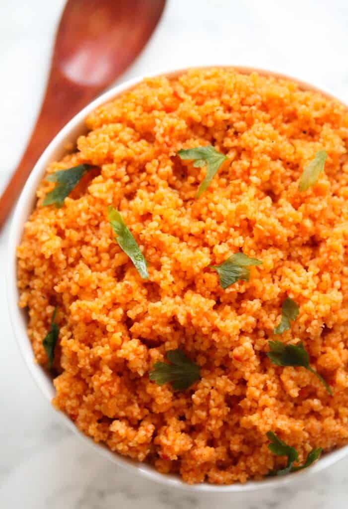 tomato couscous garnished with parsley served in a white bowl with a brown spoon on the table