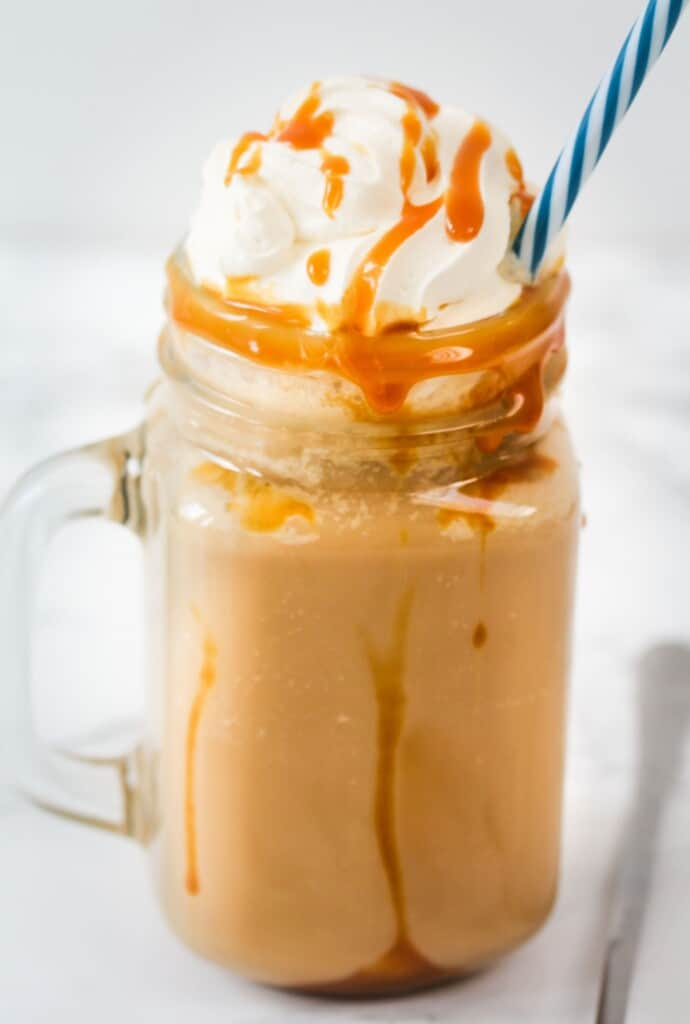 caramel Frappuccino with whipped cream and caramel sauce in a jar with a blue straw