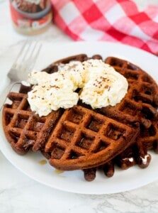 Chocolate waffles with whipped cream, maple syrup and chocolate sprinkles
