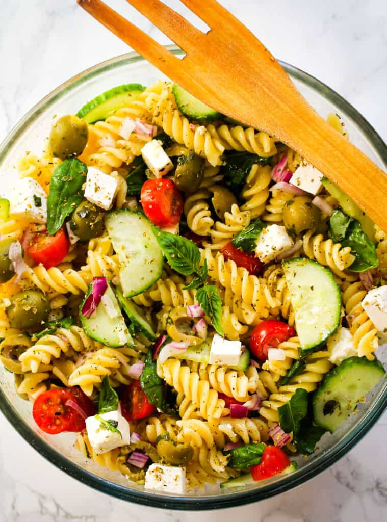 Mediterranean pasta salad in a bowl with a wooden fork