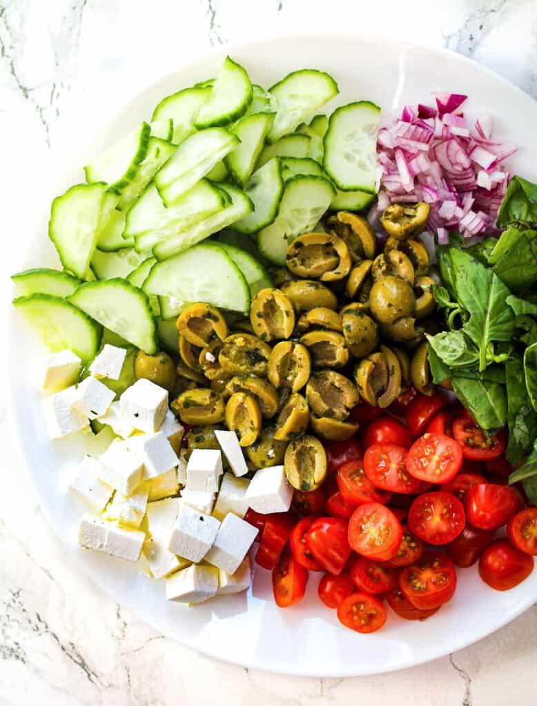 Mediterranean salad ingredients on white plate