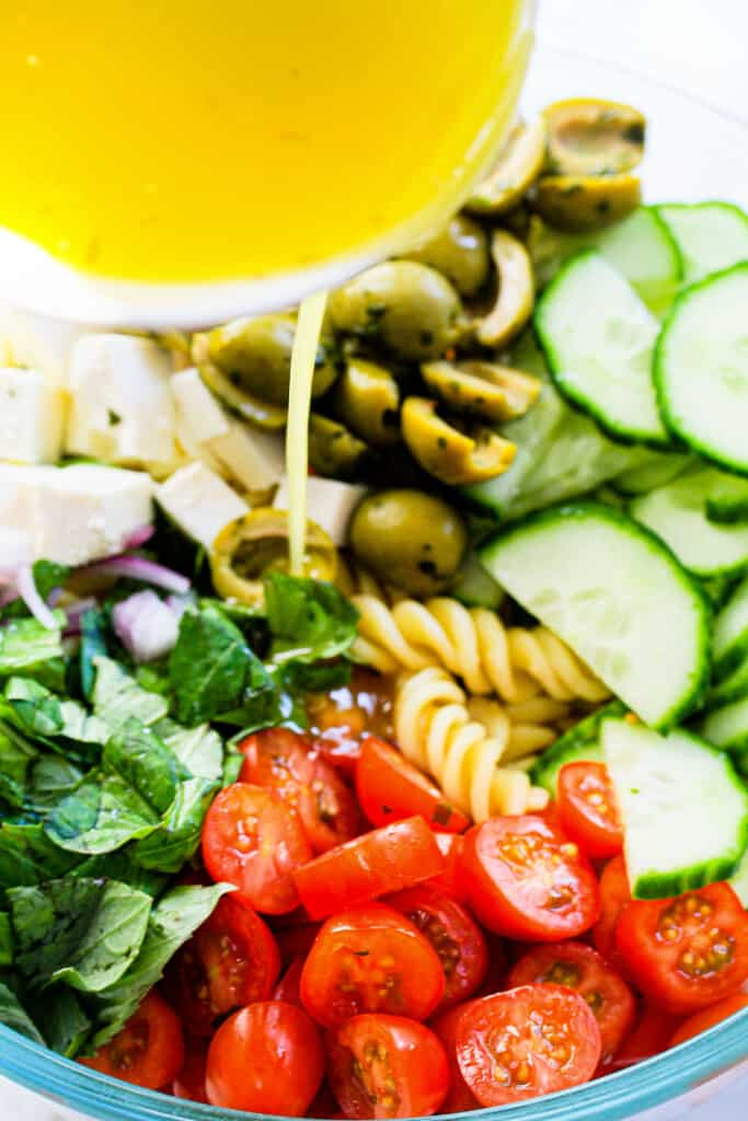lemon dressing poured into Mediterranean pasta salad