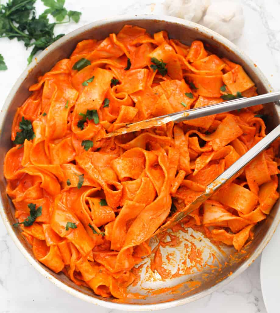 pappardelle pasta in a pan with tongs